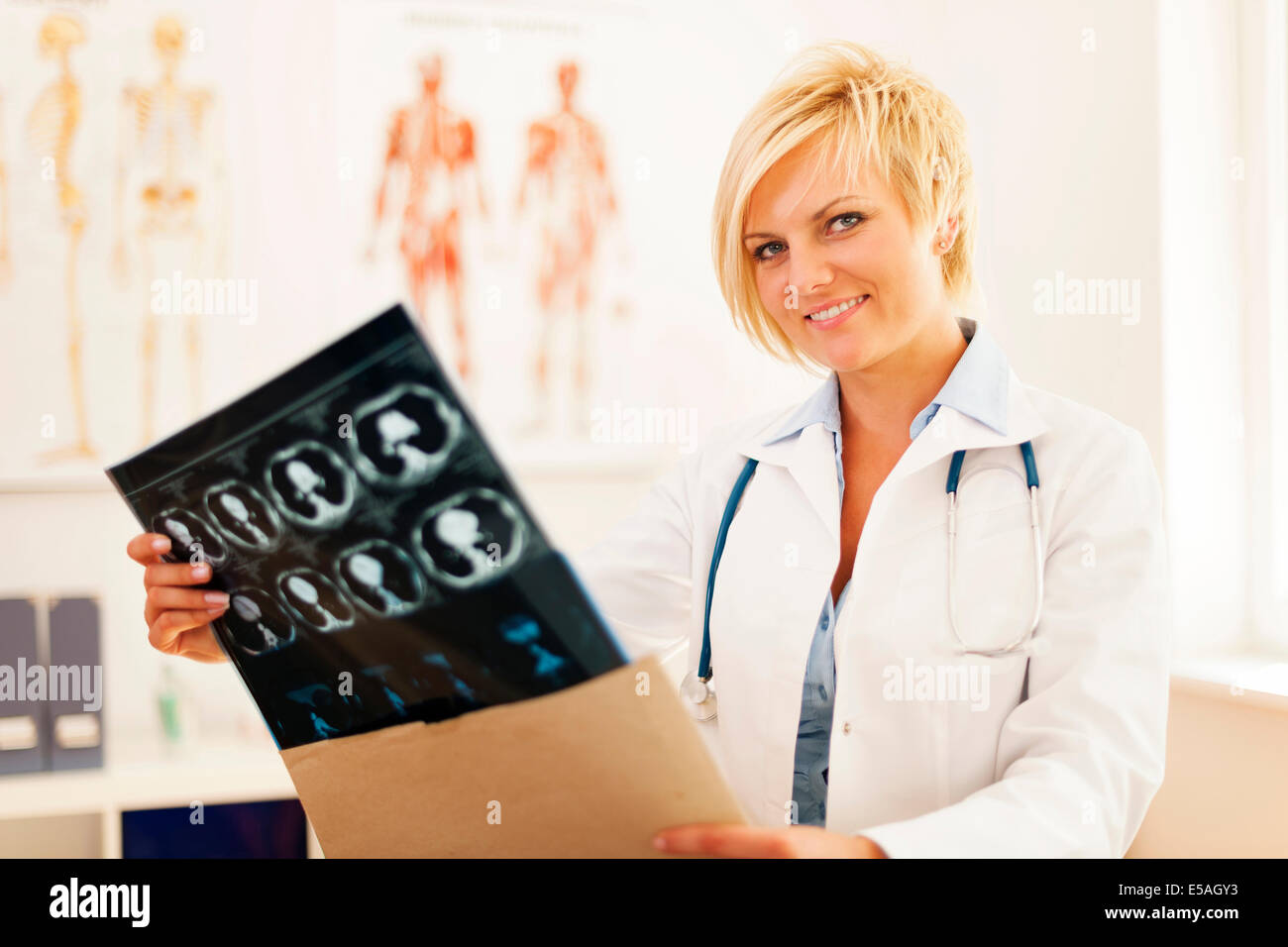 Young female doctor opening envelope with brain tomography result, Debica, Poland - Stock Image
