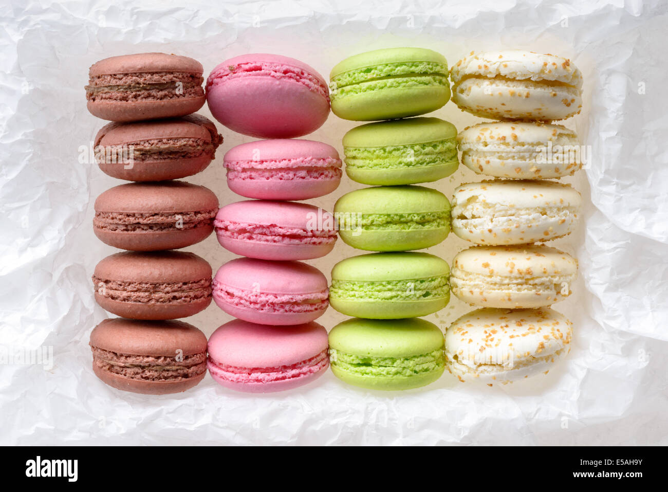 Food: multicolored macarons assortment, arranged on white crumpled paper, isolated on white background - Stock Image