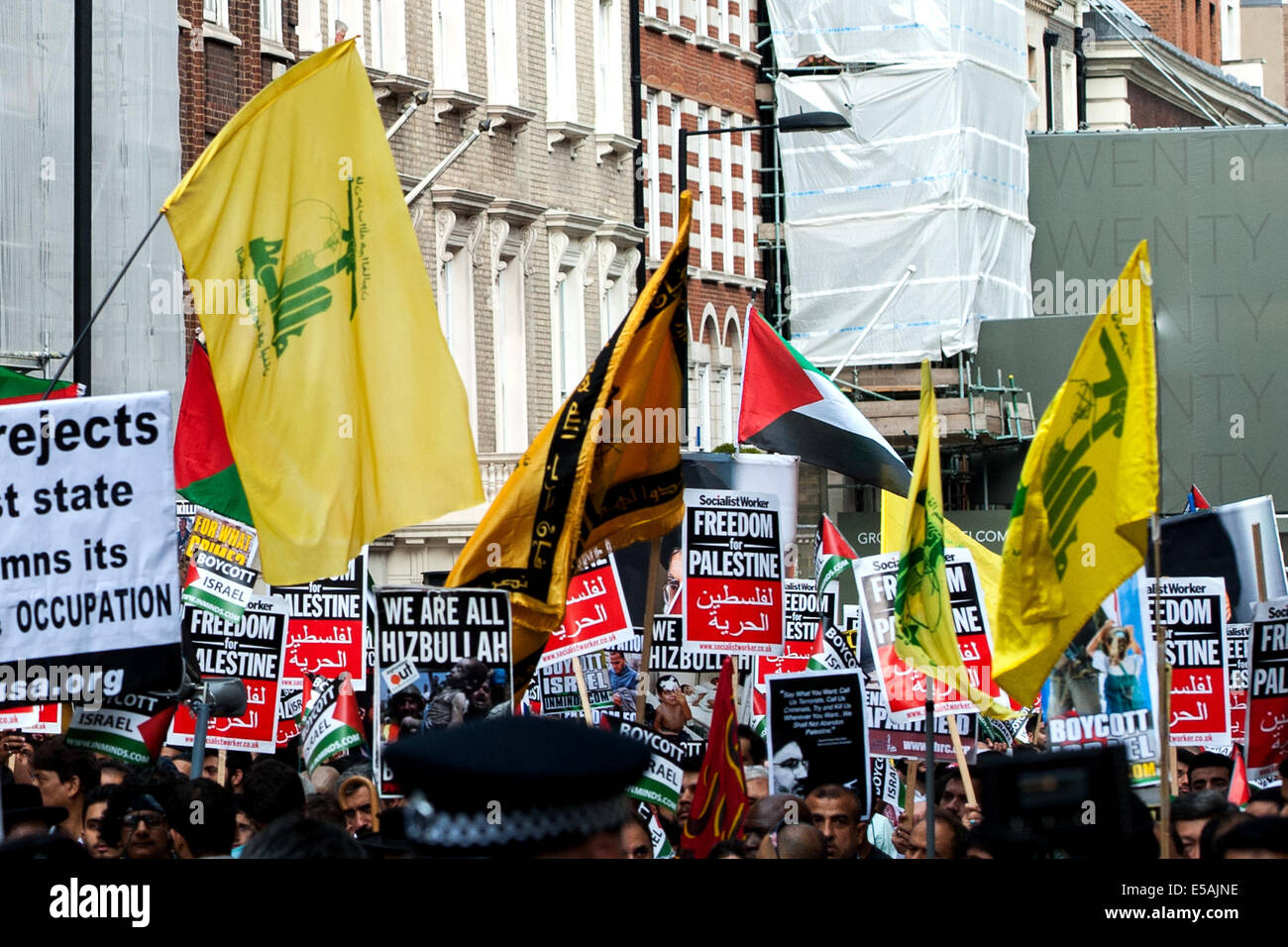 London, UK. 25th July, 2014. Hezbollah flags raised as thousands march from the BBC's Broadcasting House to - Stock Image
