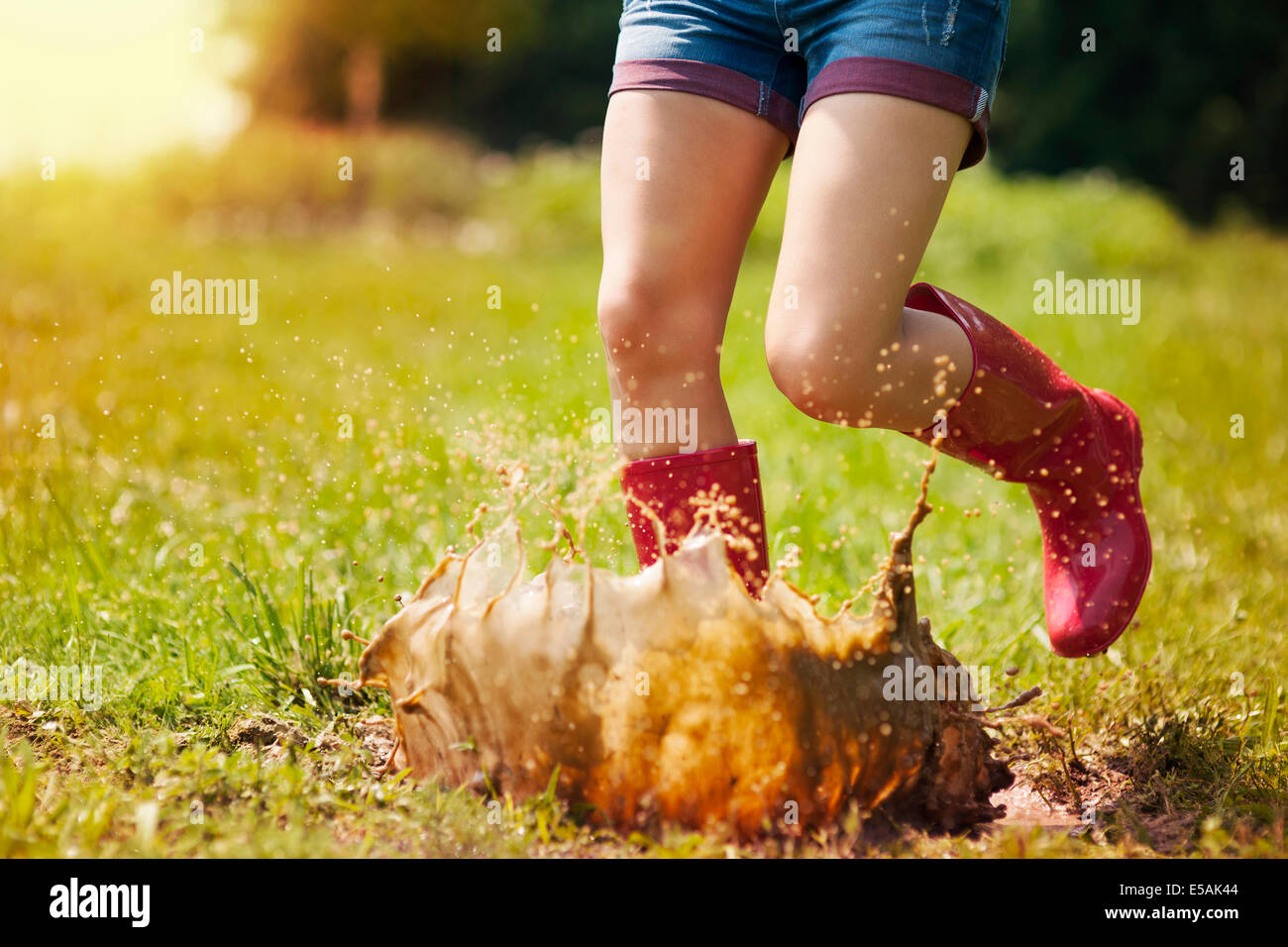 Woman have fun jumping in puddle, Debica, Poland - Stock Image