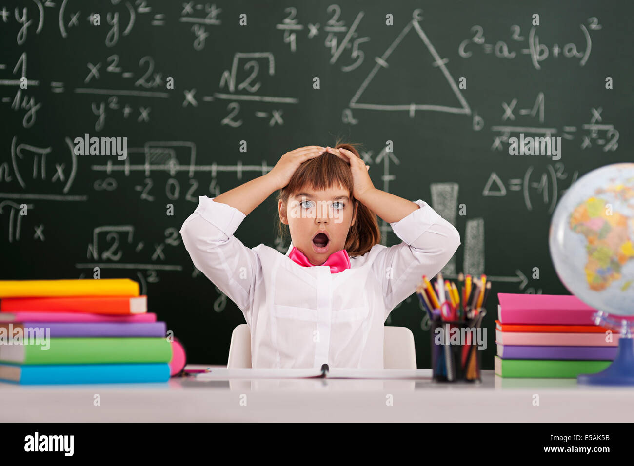 Shocked cute pupil in classroom, Debica, Poland - Stock Image