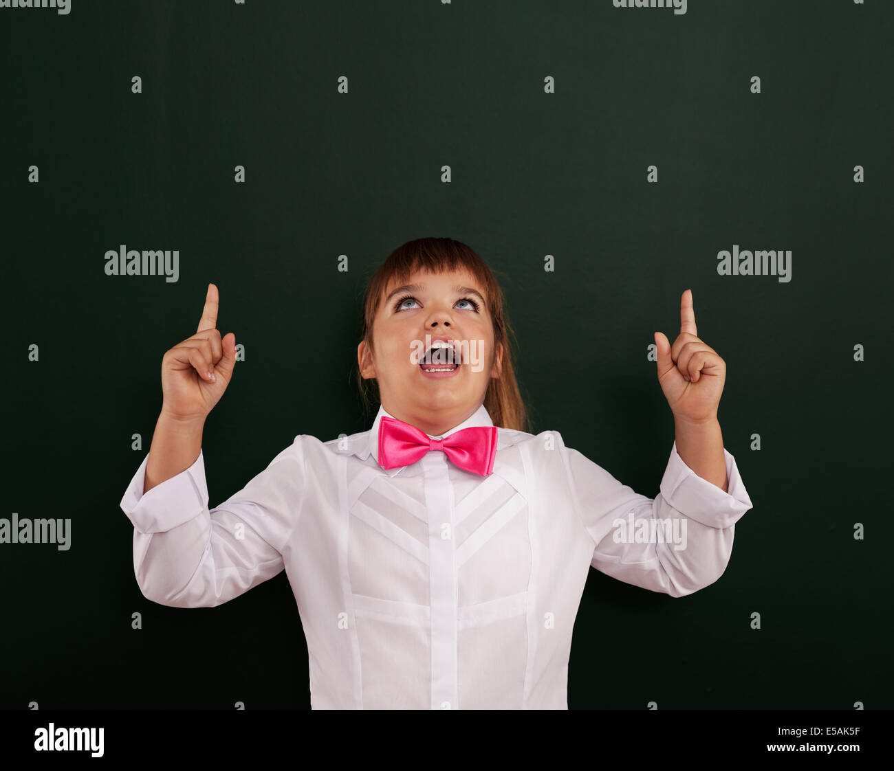 Smiling girl with pink bow tie pointing above her head, Debica, Poland. - Stock Image