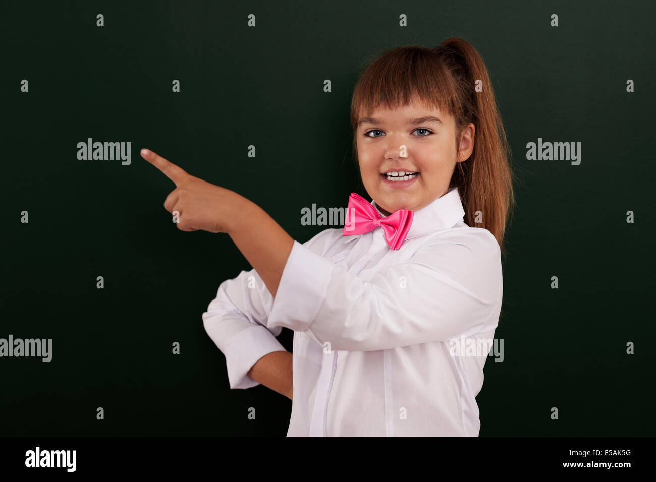 Smiling girl with pink bow tie pointing at copy space, Debica, Poland - Stock Image