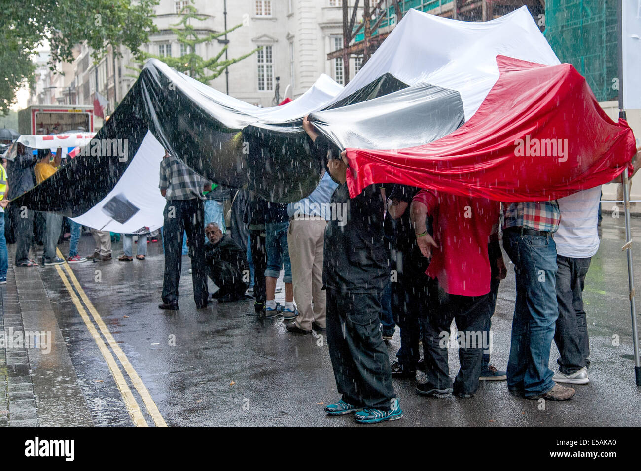 London, UK. 25th July, 2014. Protesters shelter from the rain under a large Palestinian Flag as thousands hold a - Stock Image