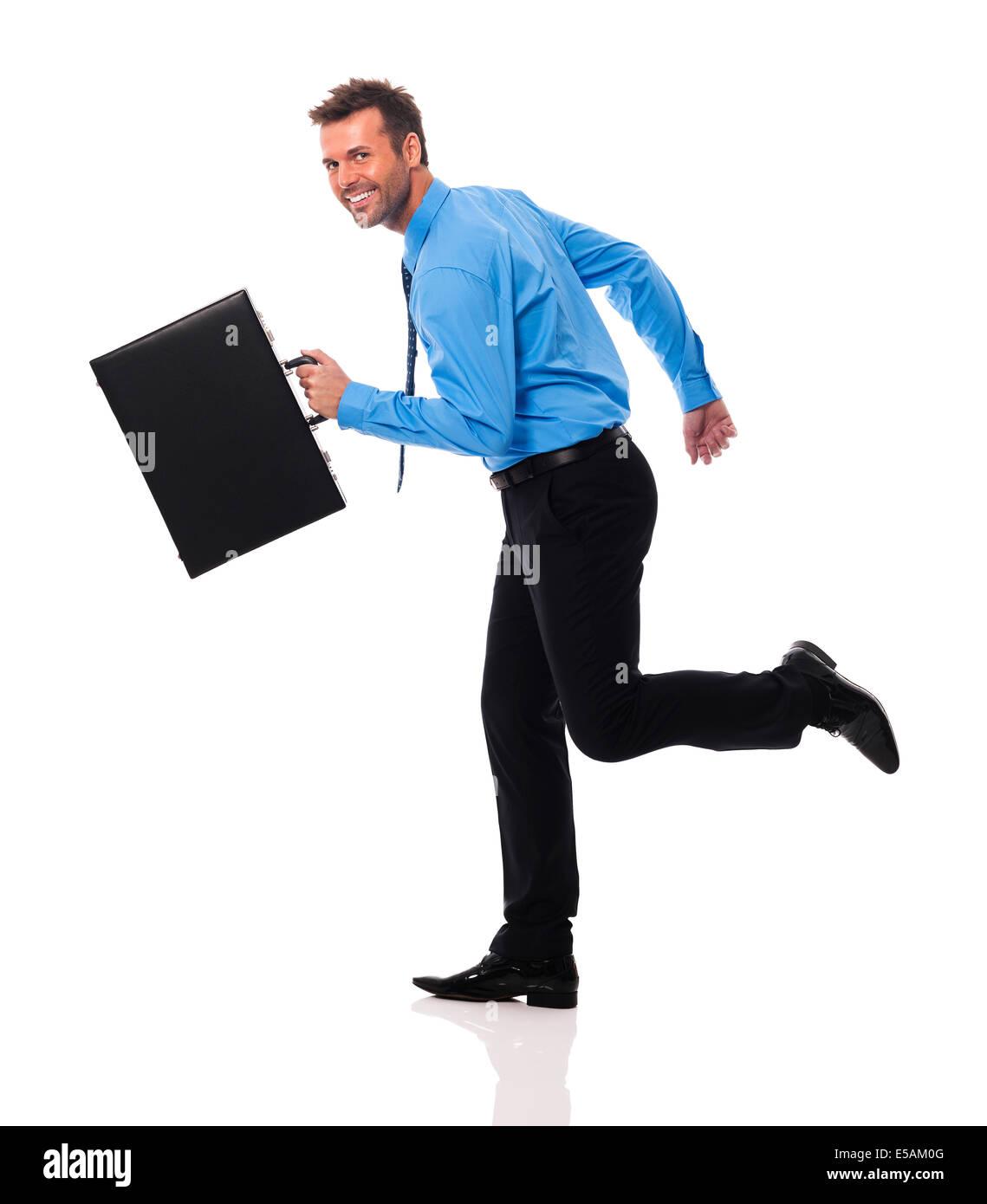 Happy businessman with briefcase running Debica, Poland - Stock Image