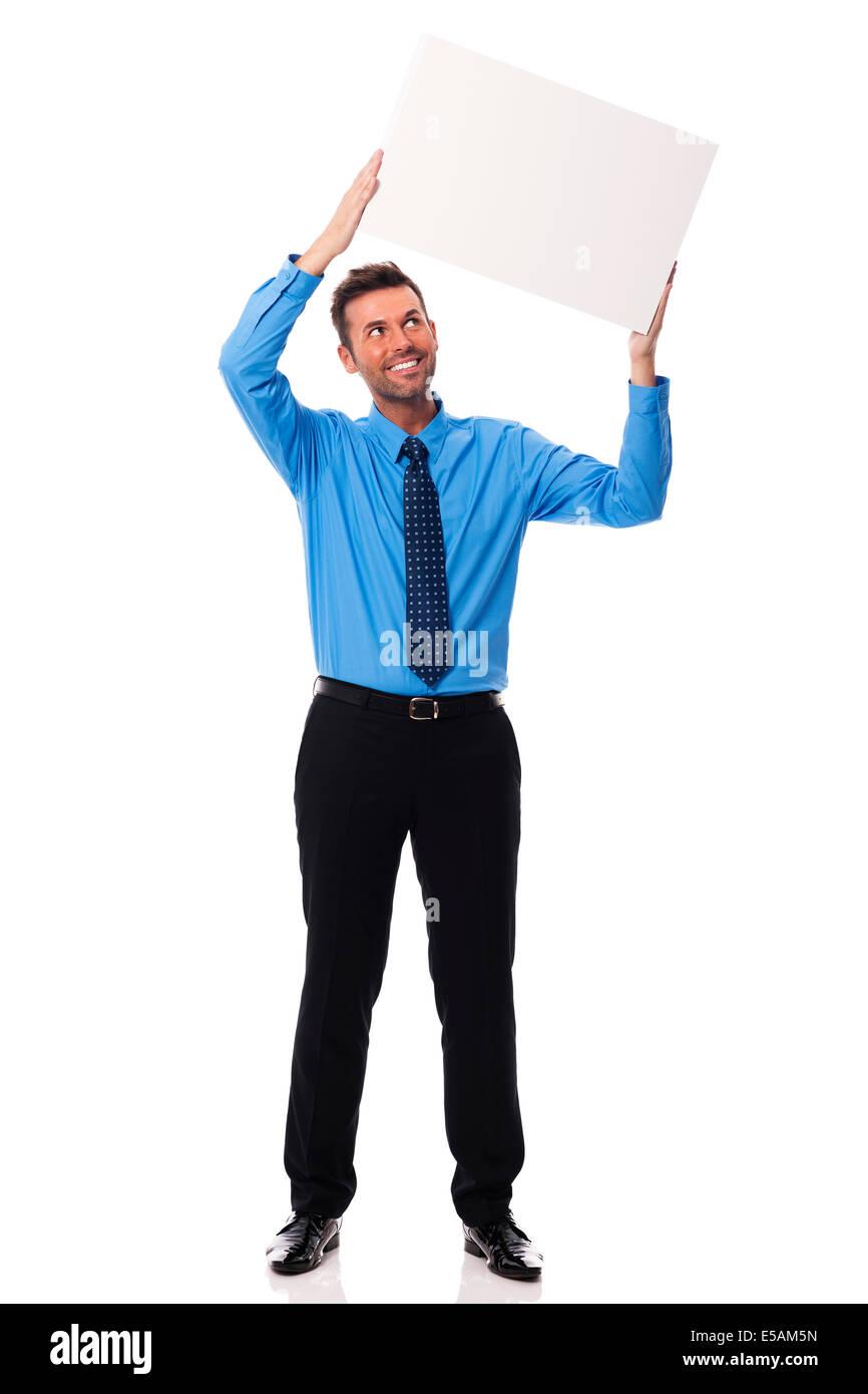 Smiling businessman holding blank placard Debica, Poland - Stock Image