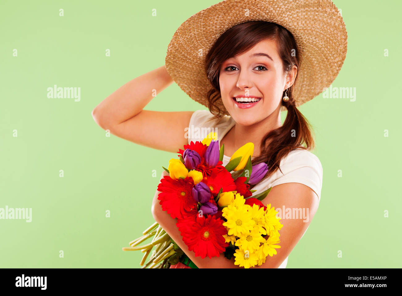 Smiling brunet woman with hat and spring flower, Debica, Poland - Stock Image