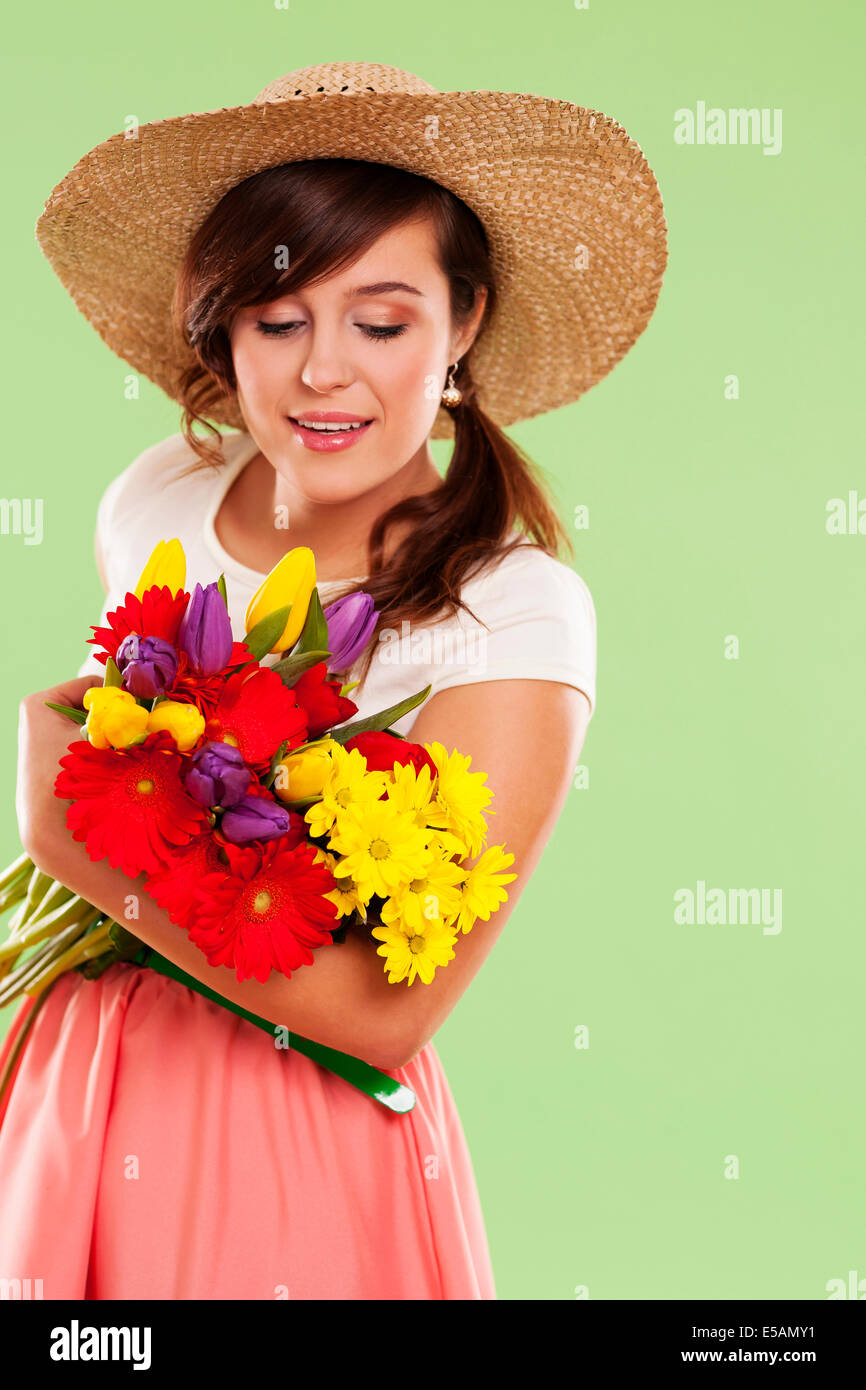 Woman wearing straw hat holding spring flower Debica, Poland - Stock Image