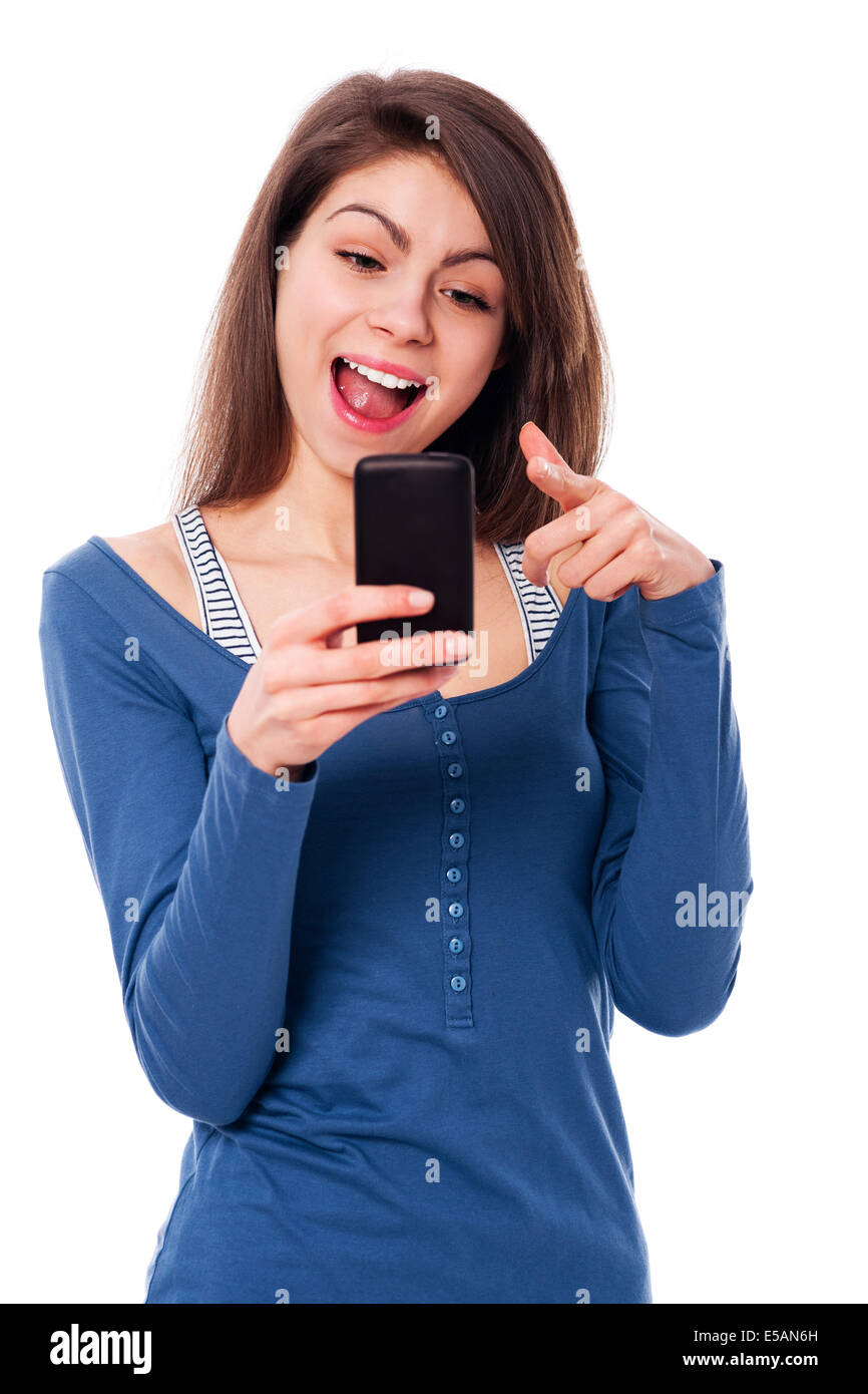 Excitement woman with mobile phone pointing at camera Debica, Poland - Stock Image