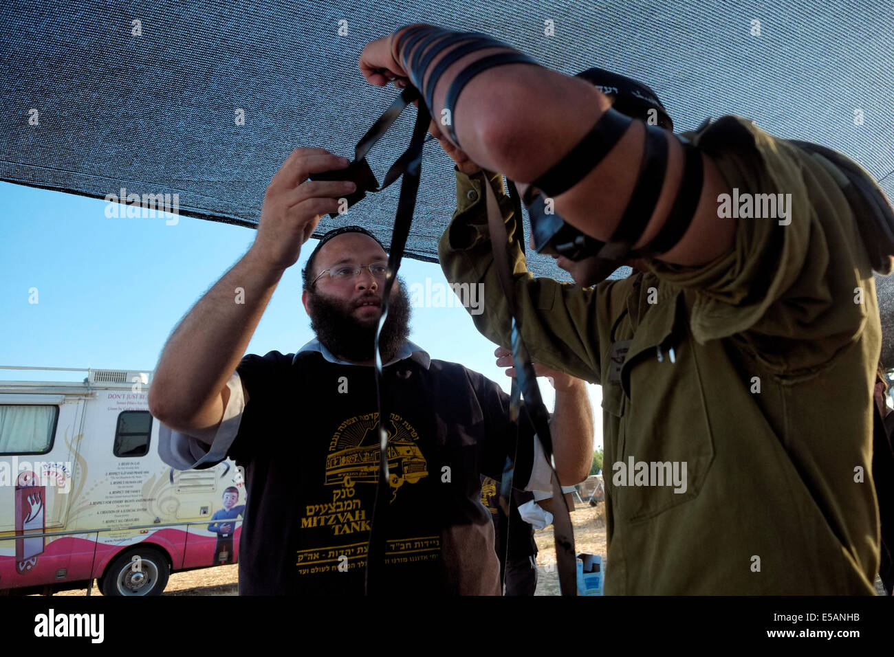 A member of Habad  religious movement helps an Israeli soldier to wear a traditional Jewish Tfilin Israel - Stock Image