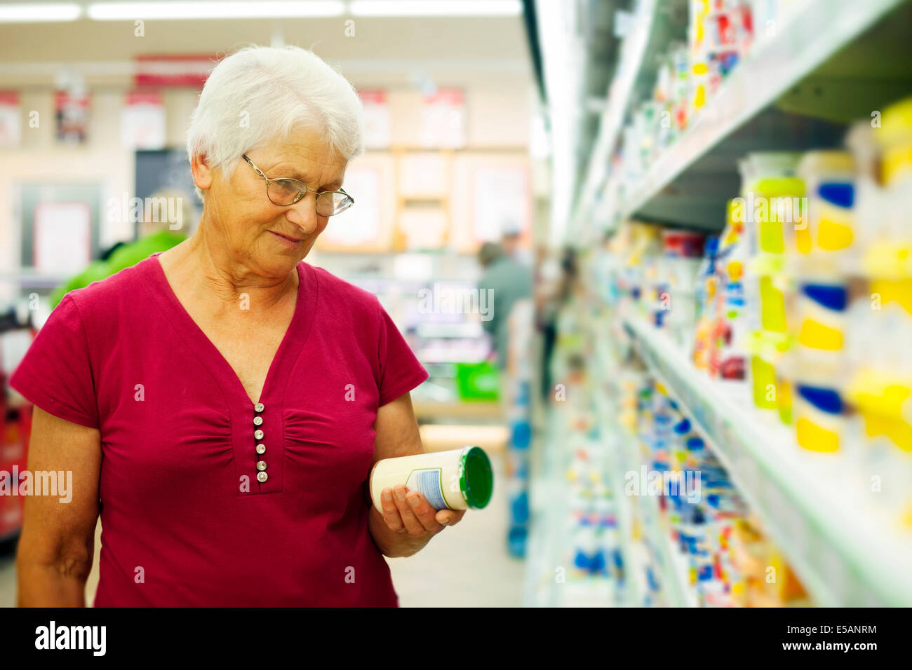Senior woman checking label on jar Debica, Poland - Stock Image