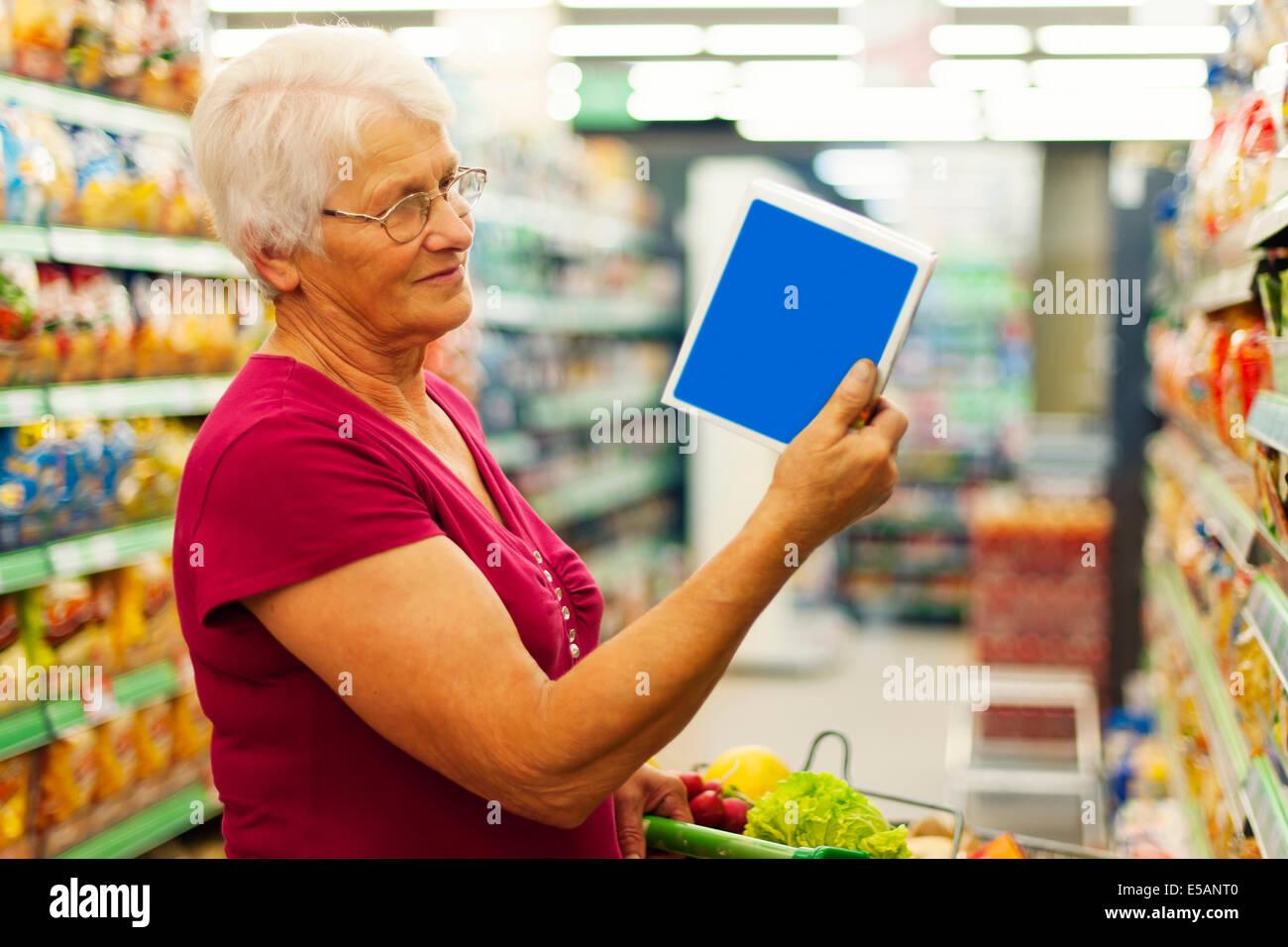 Senior woman reading description on the box, Debica, Poland - Stock Image