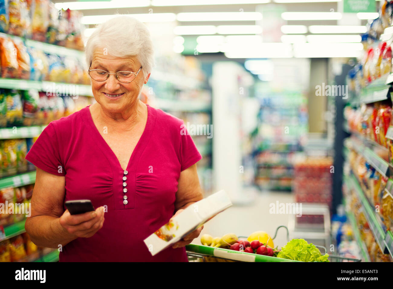 Senior woman texting on mobile phone at supermarket Debica, Poland - Stock Image