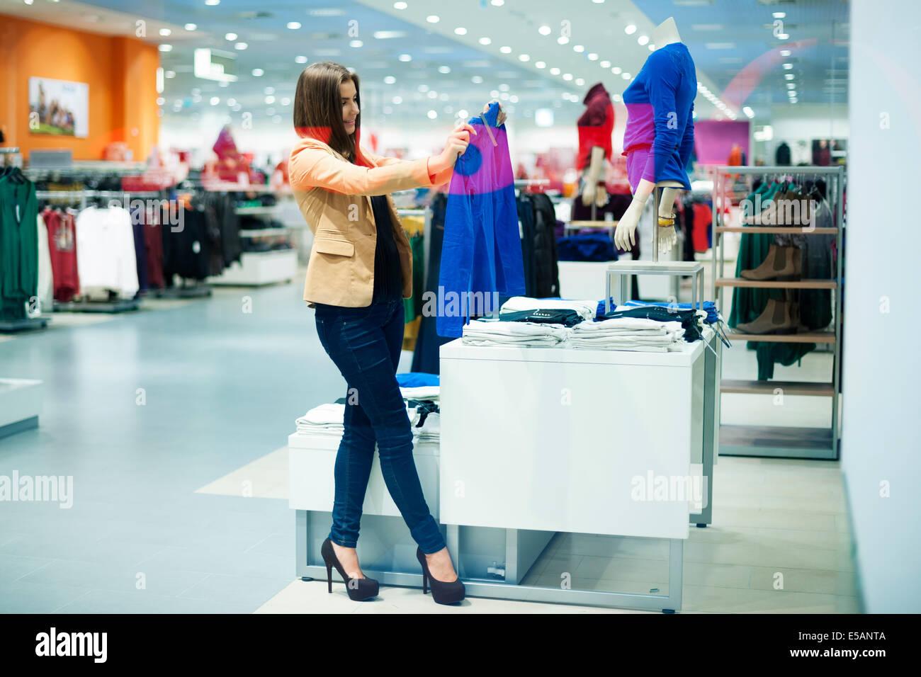 Attractive woman choosing cloths in shop Debica, Poland - Stock Image