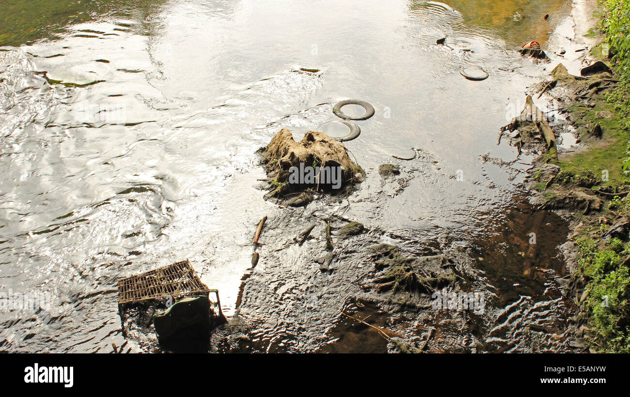 Urban canal environmental damage caused by illegally dumping rubbish such as tires and an old shopping trolley. - Stock Image