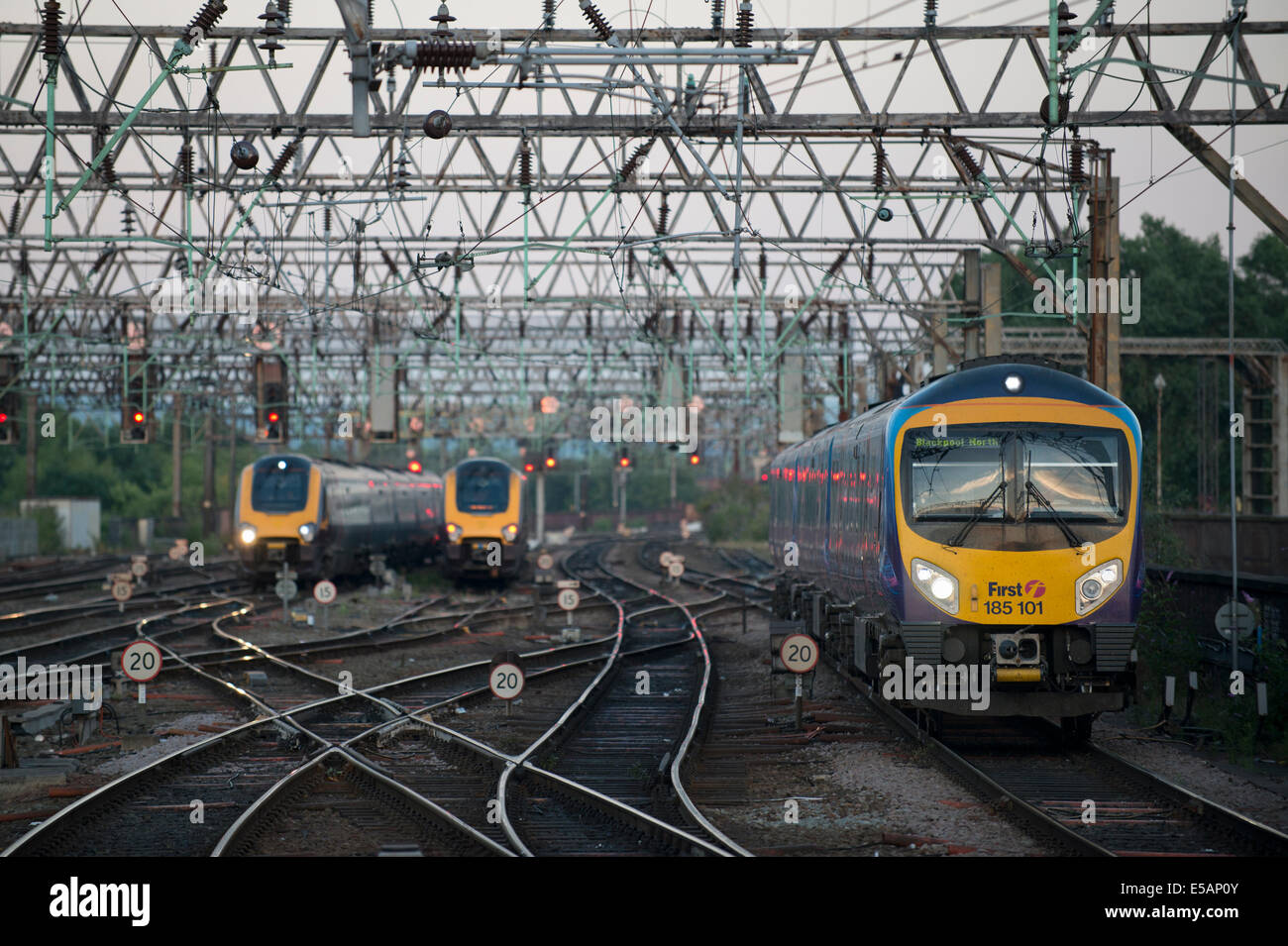 A First TransPennine Express train enters Manchester Piccadilly Rail Station as a Cross Country and Arriva train - Stock Image