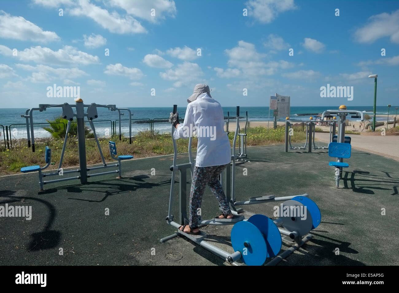 A woman working out in a gymnastic playground along the seacoast promenade in  the coastal city of Ashkelon in the - Stock Image