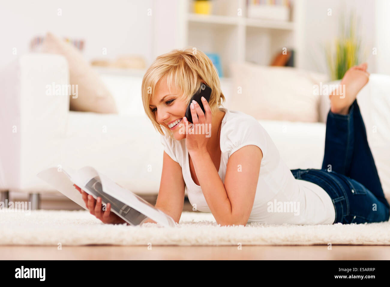 Happy woman ordering something from catalogue Debica, Poland - Stock Image