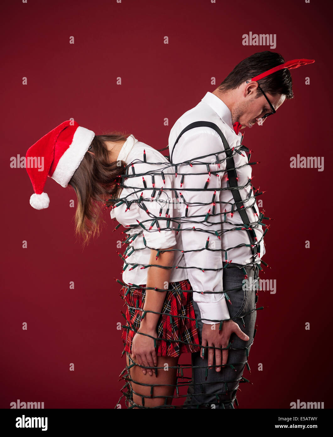 Loser nerd couple are tangling in Christmas lights  Debica, Poland - Stock Image