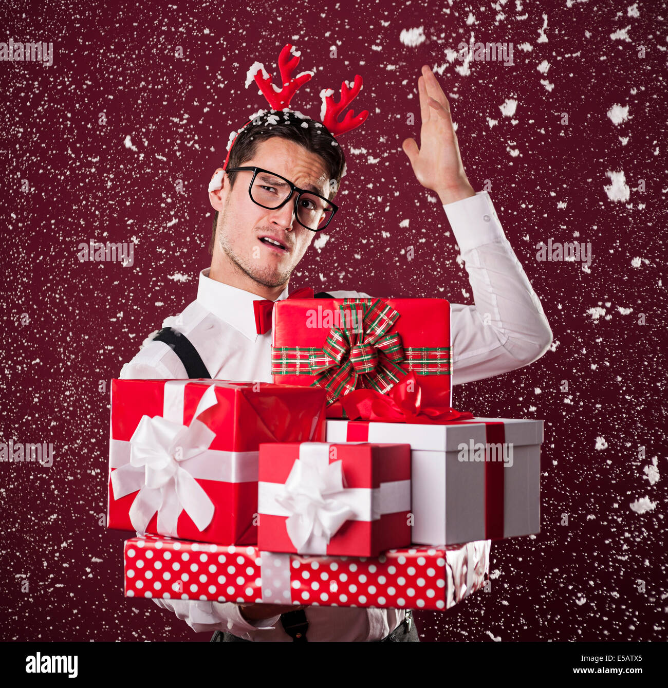 Grimacing man with stack of Christmas presents Debica, Poland Stock Photo