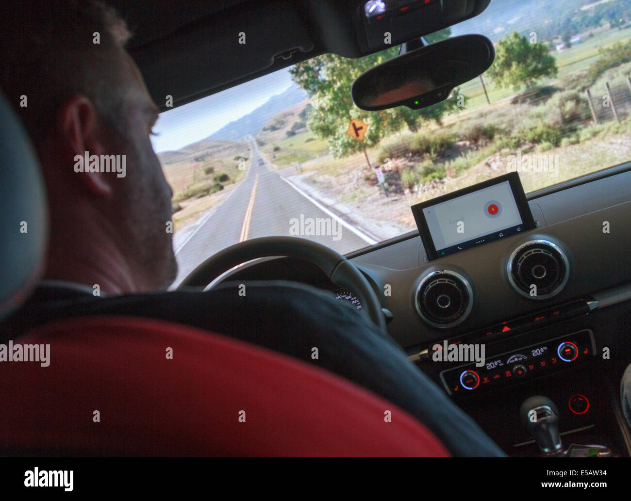Man demonstrating the use of Android Auto technology device using voice commands to navigate and control entertainment - Stock Image
