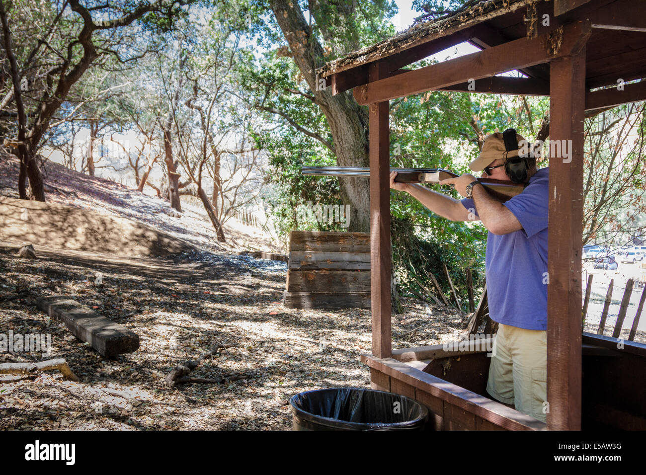 Man shooting sporting clays with his shotgun on a course in the woods in California - Stock Image