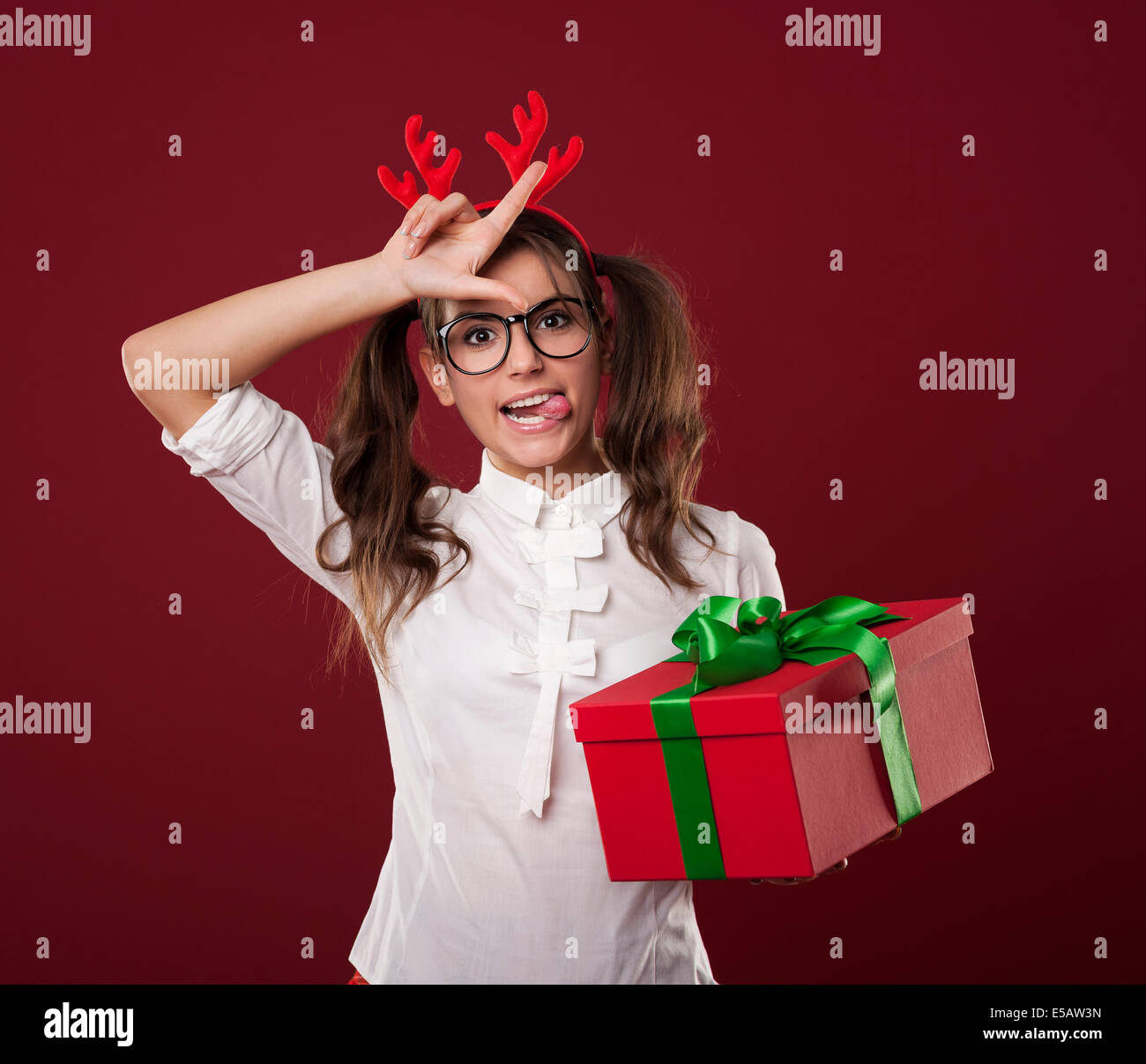 Nerdy woman with Christmas gift showing loser sign Debica, Poland - Stock Image