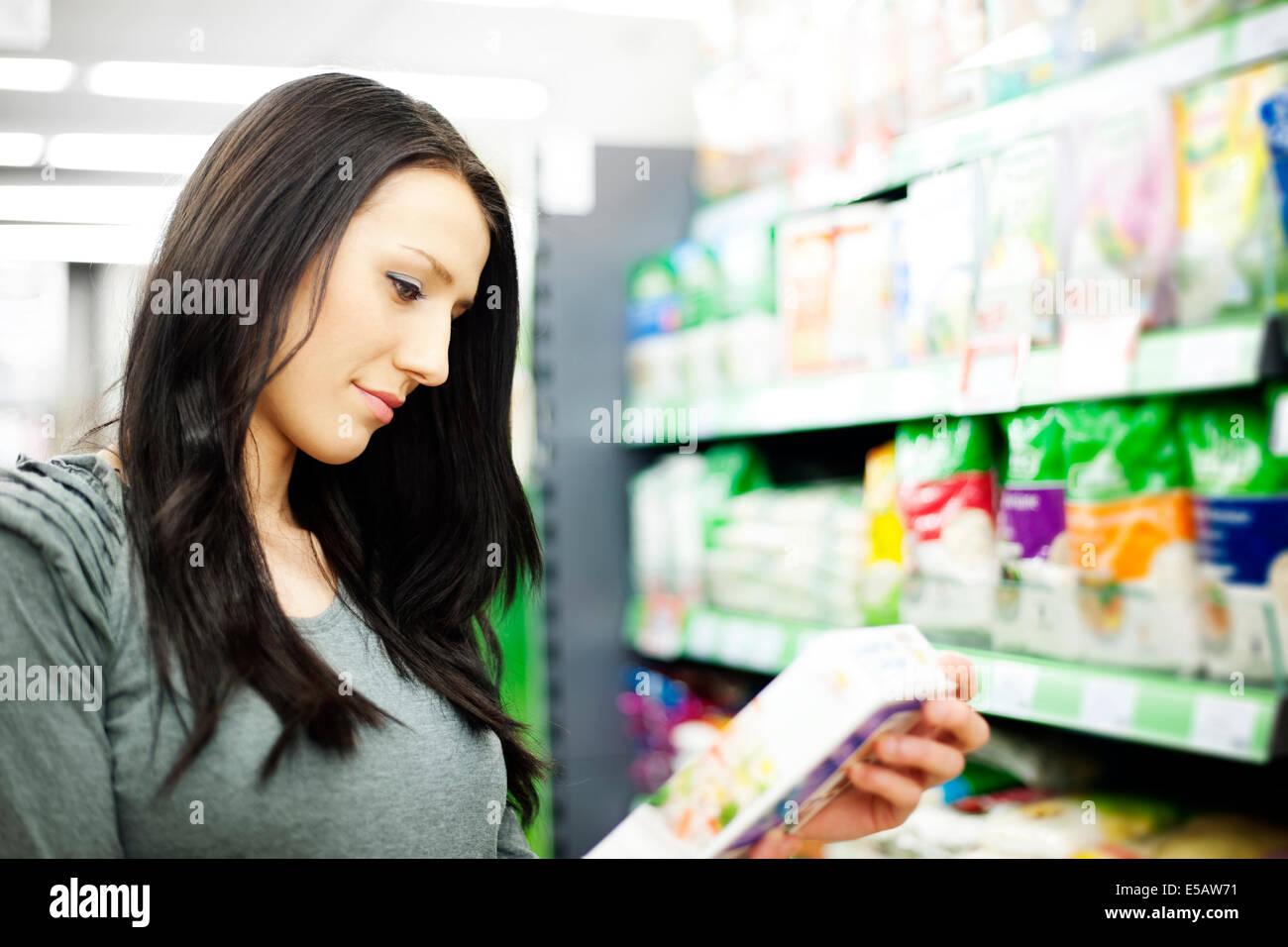 Woman reading description on the box Debica, Poland - Stock Image