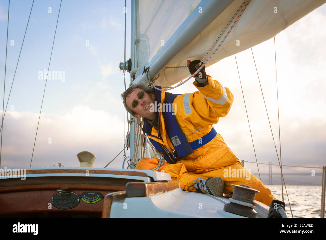 Sailor in yellow foul weather gear checking the lines of the mainsail as he heads into cloudy weather in his sailboat - Stock Image