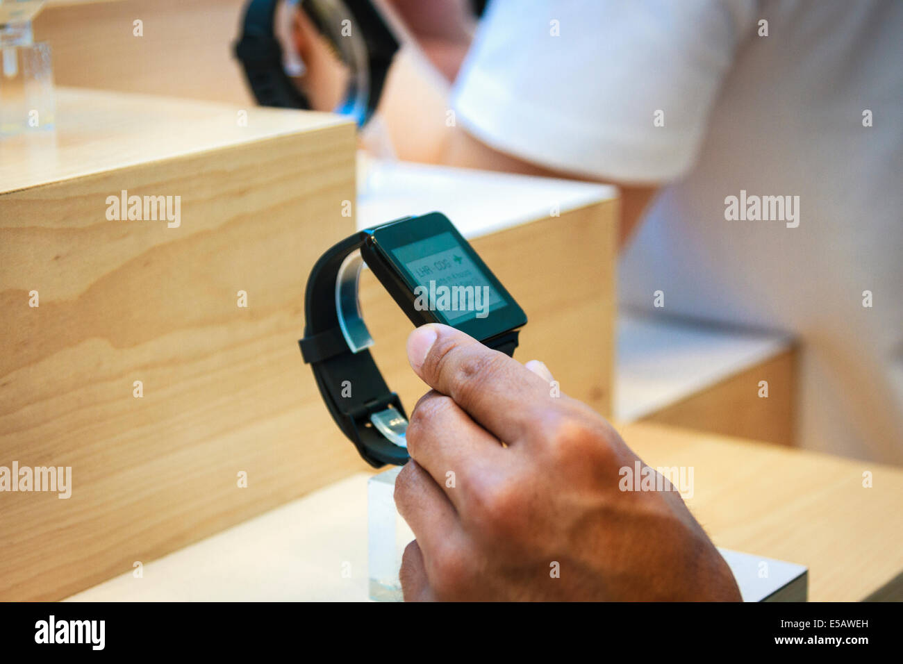 Male hand touching Samsung Gear Live smartwatch wearable technology in a display at Google I/O conference in San - Stock Image