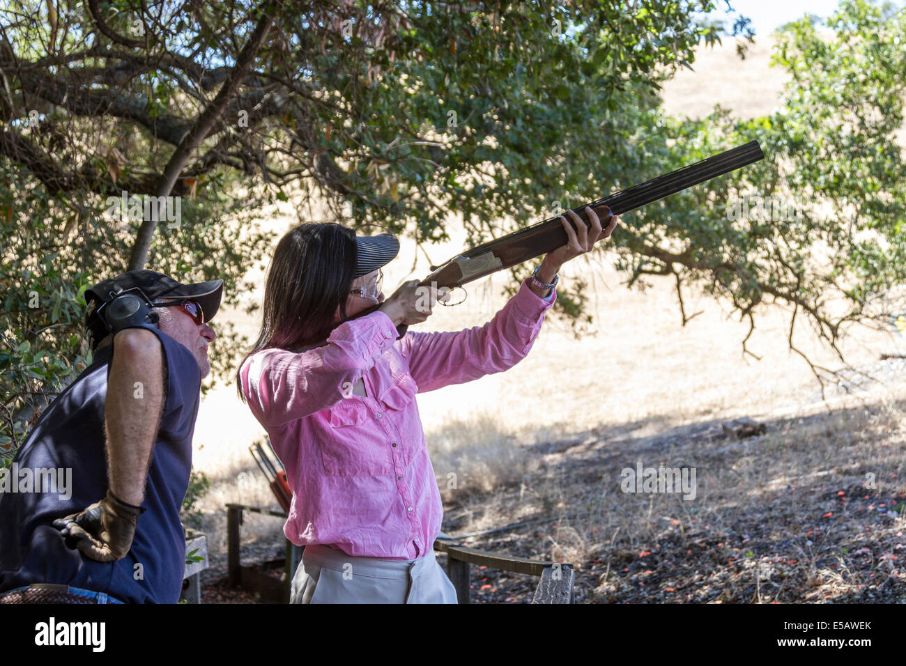 Asian woman shooting clays with a shotgun as instructor teaches her how to shoot - Stock Image