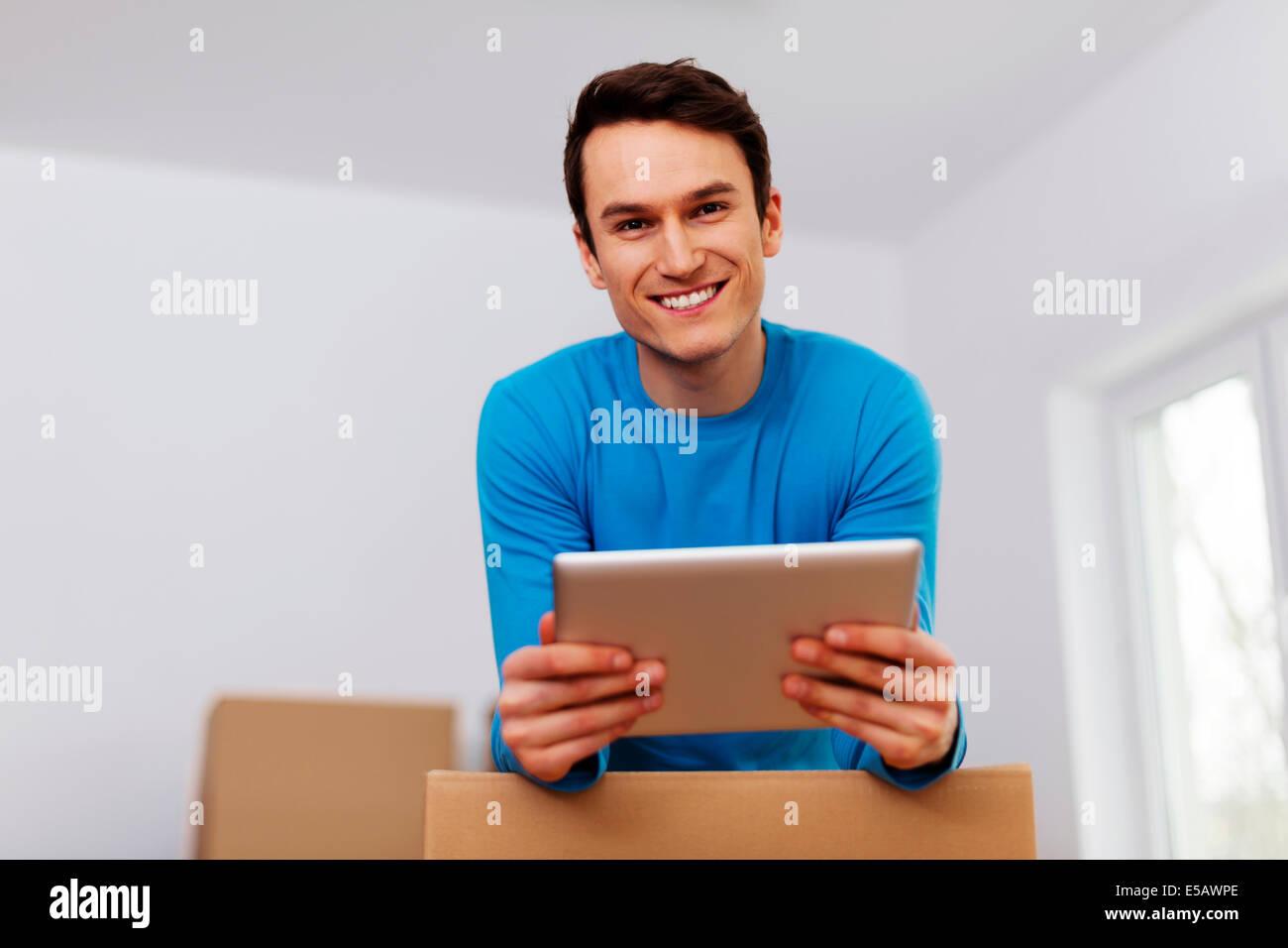 Happy man organize relocation in his new apartment  Debica, Poland - Stock Image