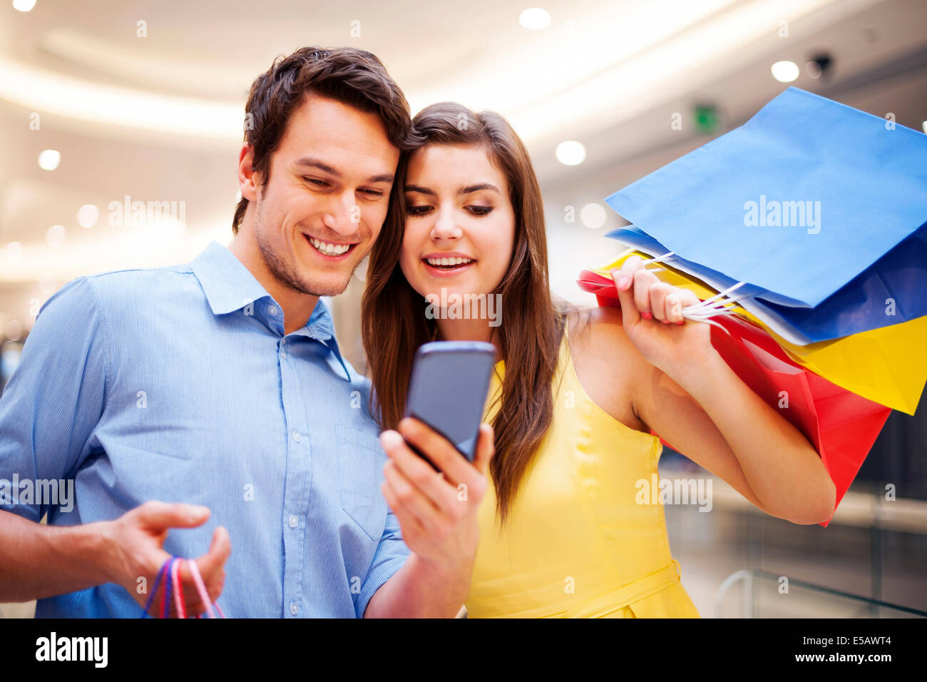 Smiling couple checking something on the mobile phone Debica, Poland - Stock Image