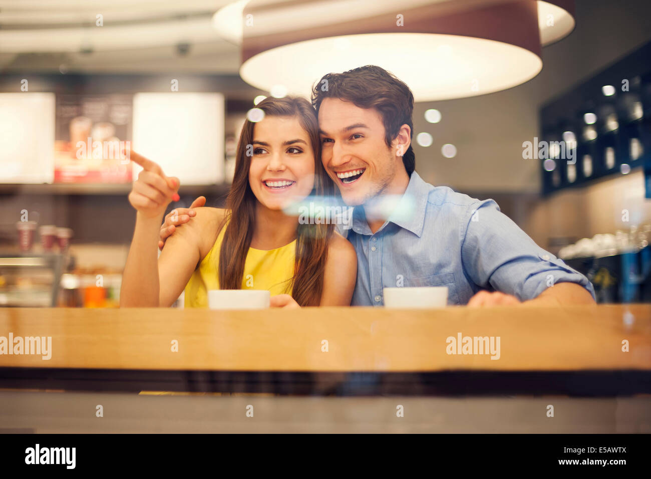 Happy young couple in cafe pointing to something Debica, Poland - Stock Image