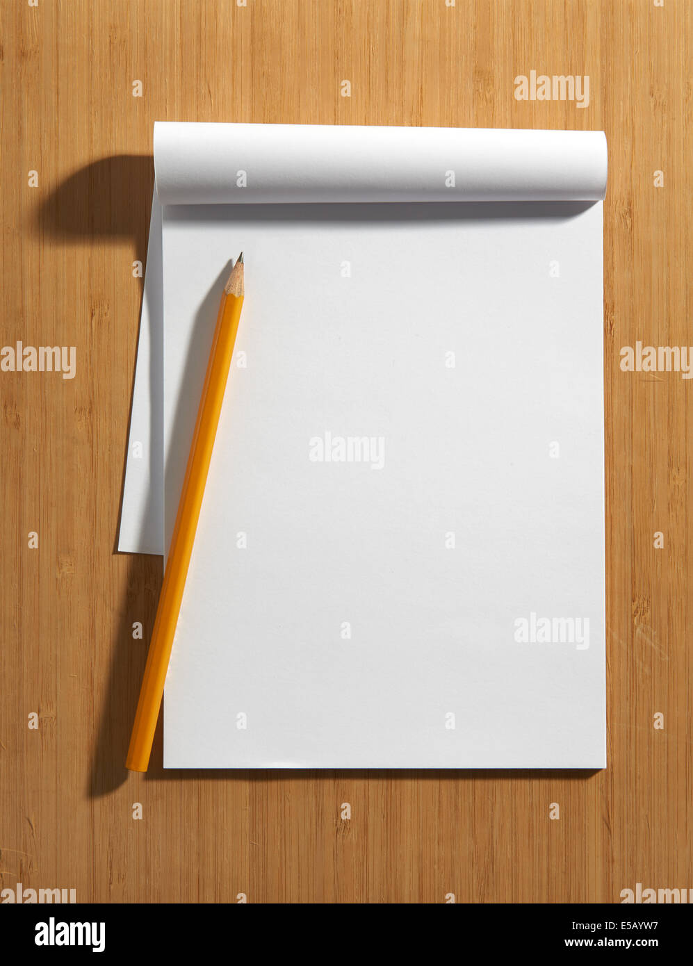 Overhead view of a blank white page of a notepad with copy space and a pencil lying on a wooden surface - Stock Image
