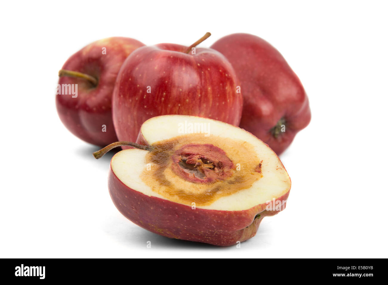 rotten cut red apple on a white background - Stock Image