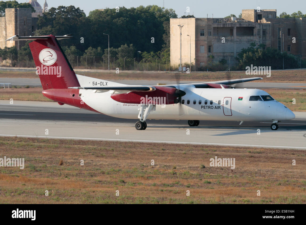 De Havilland Canada Dash 8 turboprop commuter aircraft of the Libyan operator Petro Air on the runway after landing - Stock Image