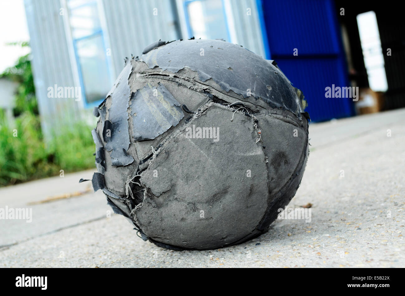 Old football ball badly ragged Stock Photo