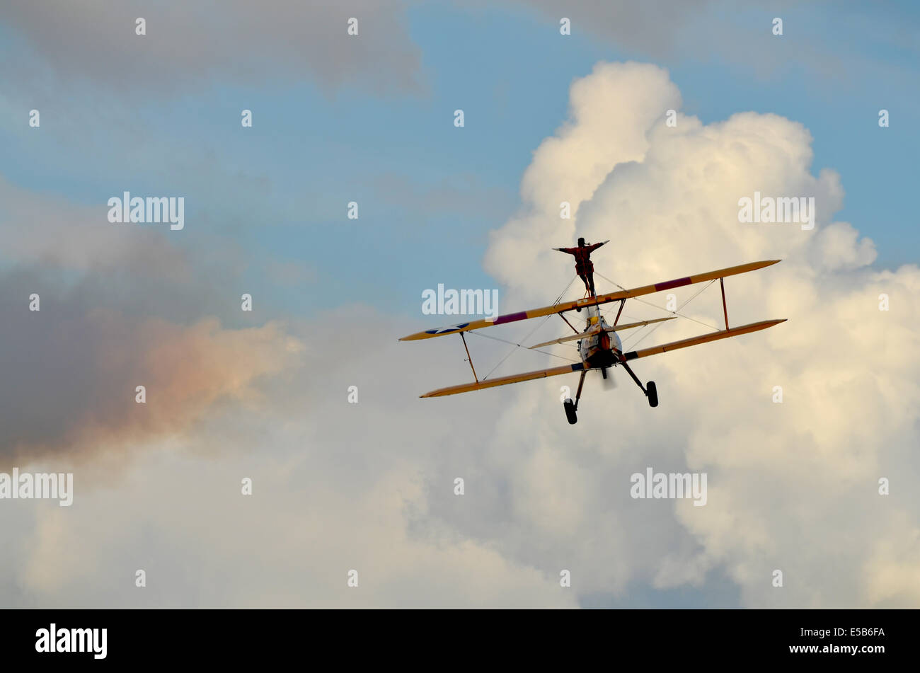 Wing walker on a yellow bi-plane flying away. - Stock Image
