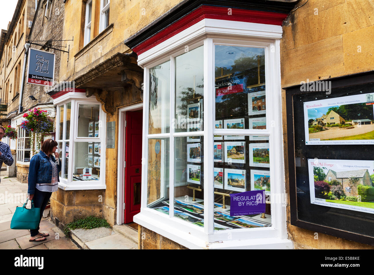Cotswolds estate agents store customer looking through window selling homes houses in the UK England - Stock Image