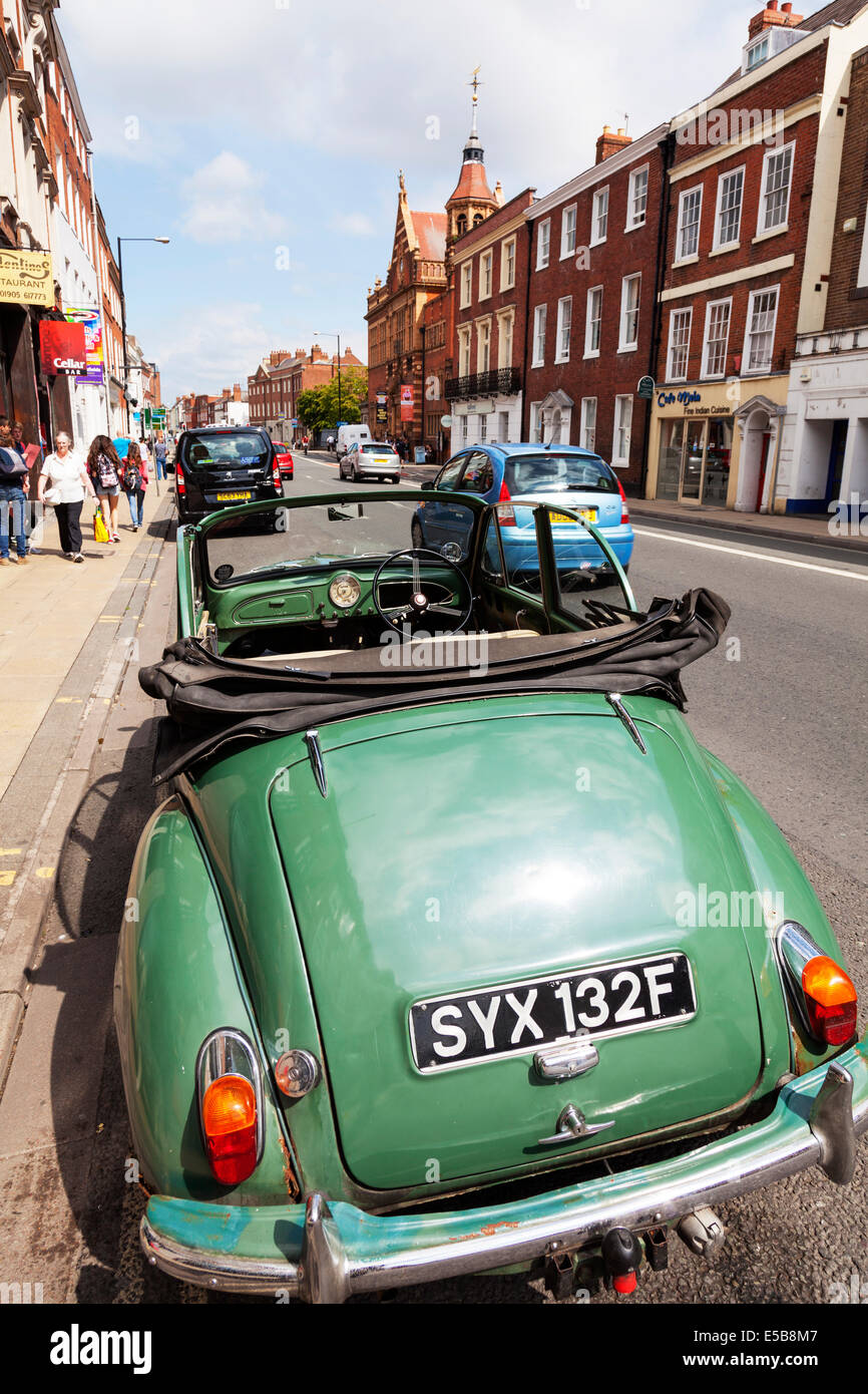 Morris Minor 1000 convertible soft top green parked outside high street Worcester City UK England - Stock Image