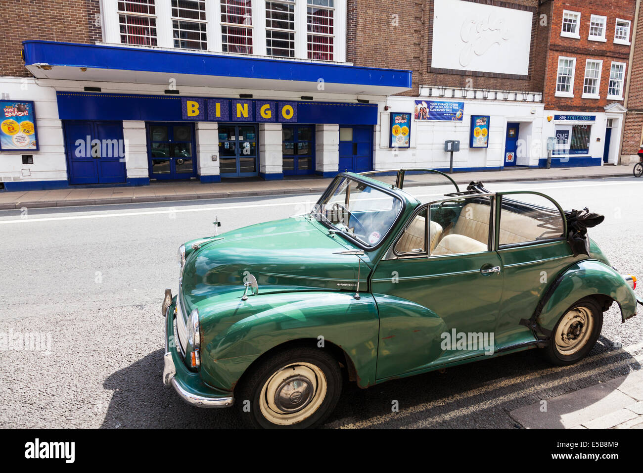 Morris Minor 1000 convertible soft top green parked outside gala bingo hall Worcester City UK England - Stock Image