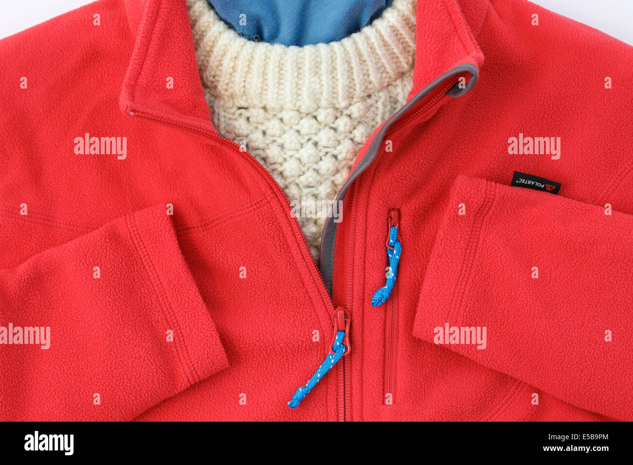 Red Polartec fleece jacket with zip open over an Arran sweater for warm winter clothing. England, UK, Britain - Stock Image