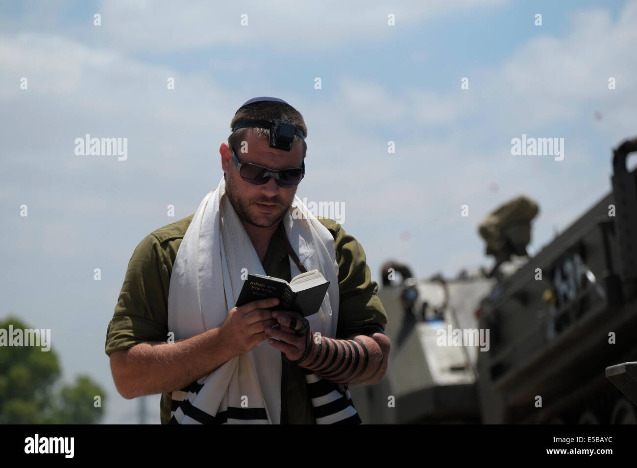 An Israeli soldier wrapped with traditional Jewish Tfilin and praying near the border with Gaza Israel - Stock Image