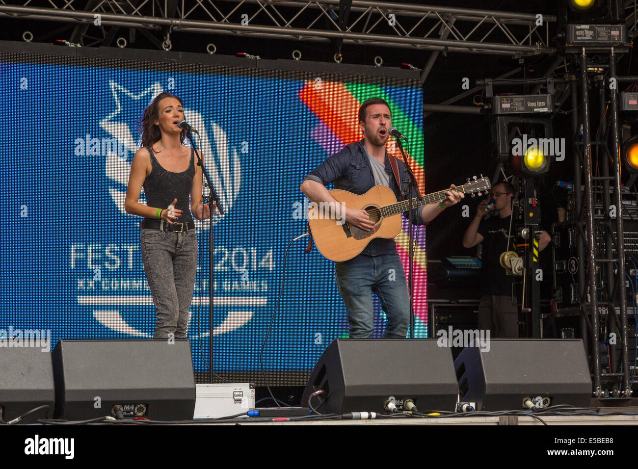 Man And Woman Perform On Stage Singing With Acoustic Guitar West