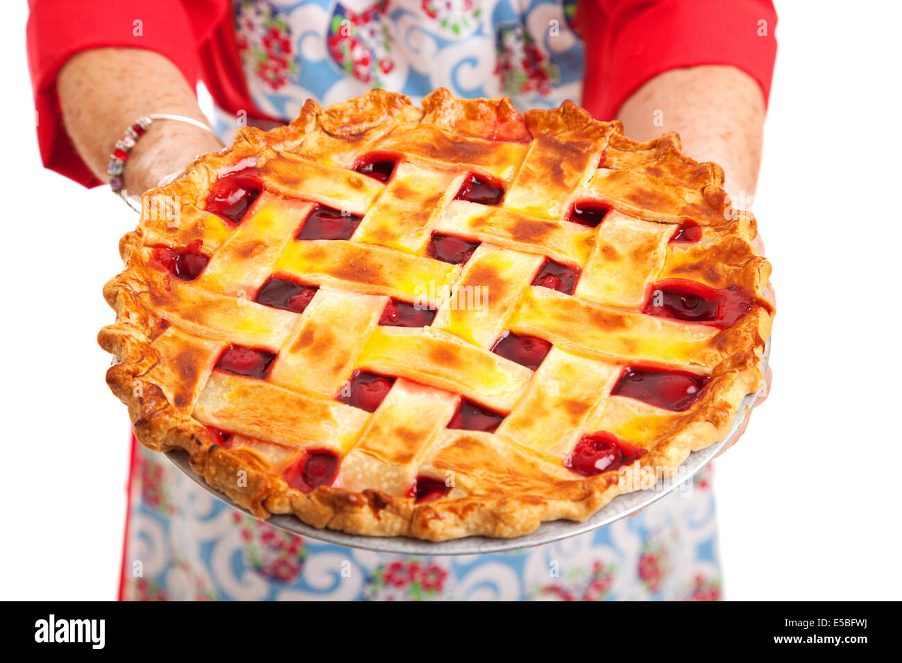 9c27d19d Closeup of a homemade cherry pie being held by a stereotypical grandma.  Isolated on white