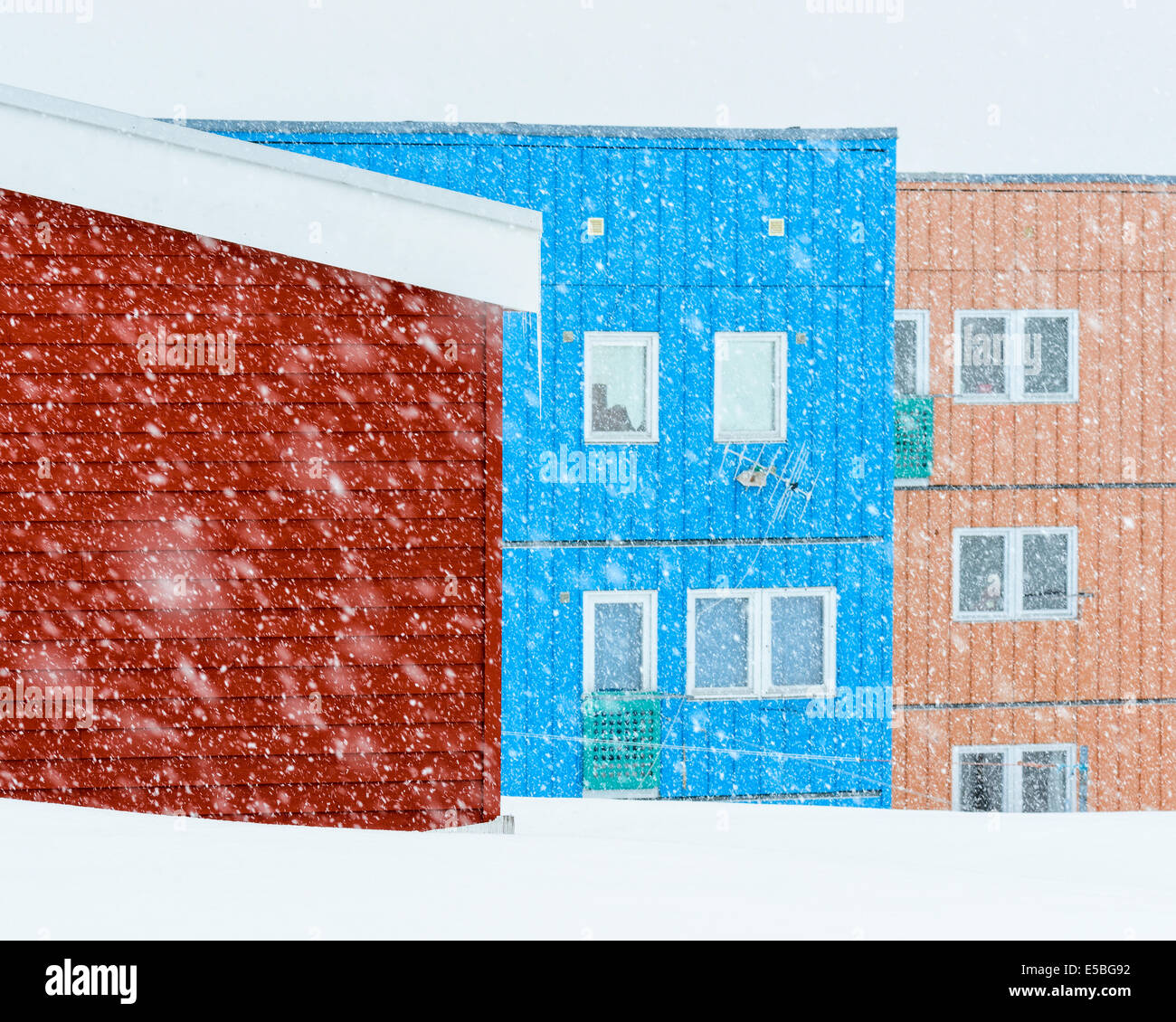 Snowfall in front of colorful residential area - Stock Image