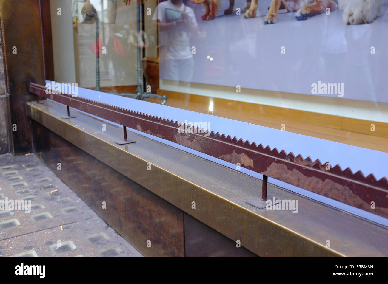 serrated metal bar to prevent people sitting or sleeping on shop window ledge - Stock Image