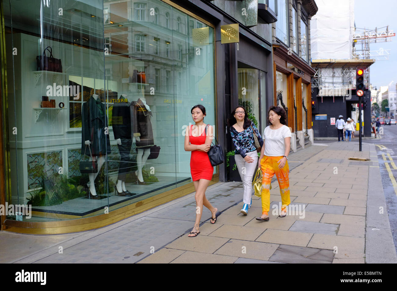 attractive young Chinese woman in red mini dress  with older women on Bond Street - Stock Image