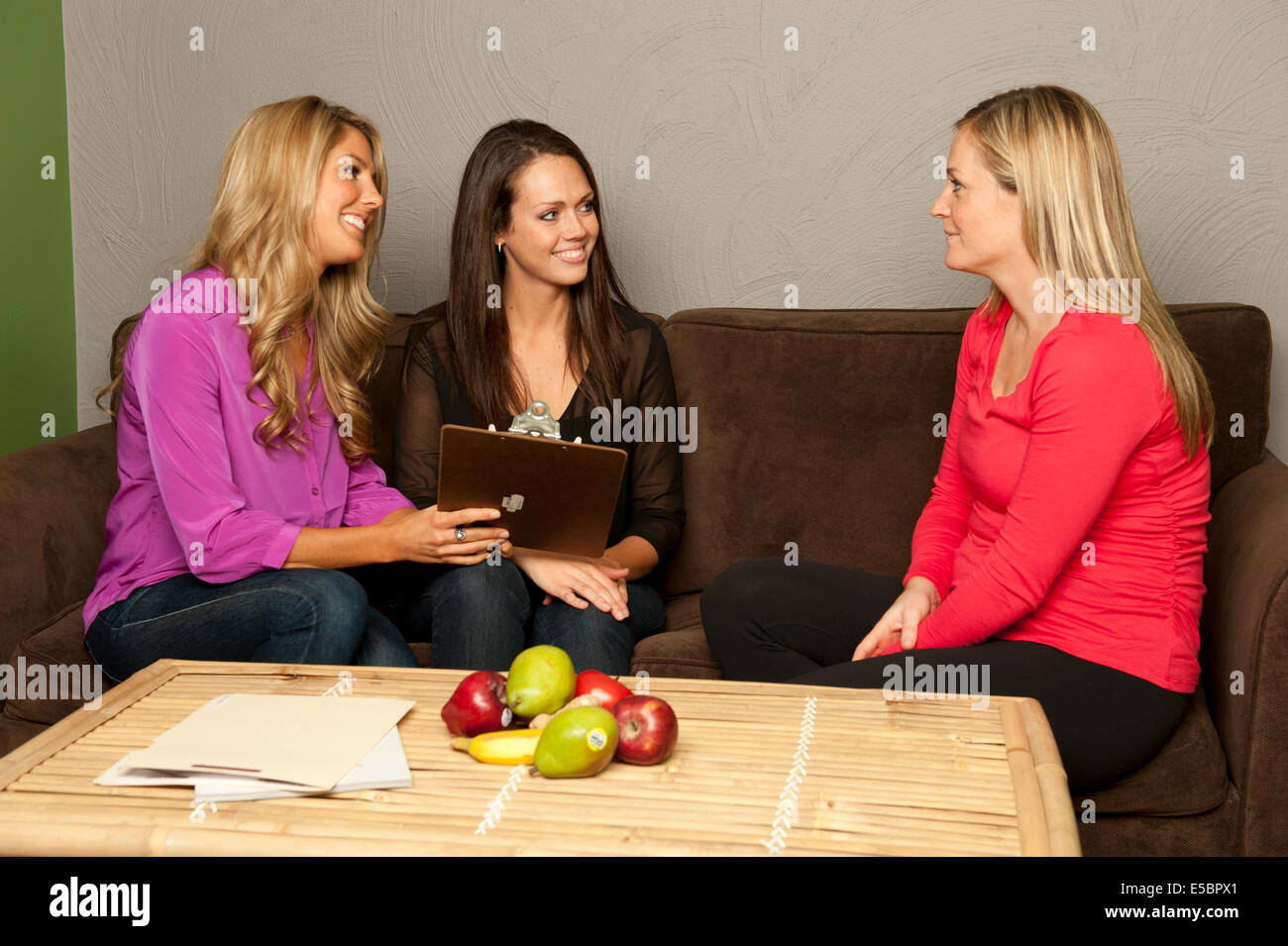 A pair of nutritionist consult a pregnant female on a couch. Stock Photo